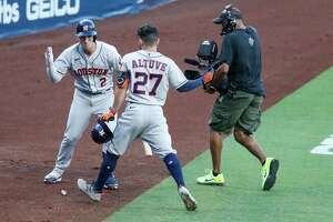 Houston Astros Alex Bregman (2) high fives Jose Altuve (27) after Altueve hit a solo hoe run off Tampa Bay Rays Blake Snell during the first inning of Game 1 of the American League Championship Series at Petco Park Sunday, Oct. 11, 2020, in San Diego.