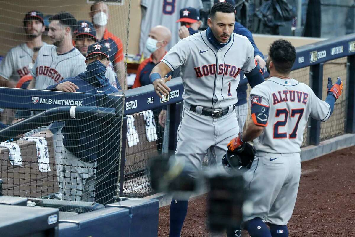 Houston Astros Carlos Correa (1) high fives Jose Altuve (27) after Altuve hit a solo hoe run off Tampa Bay Rays Blake Snell during the first inning of Game 1 of the American League Championship Series at Petco Park Sunday, Oct. 11, 2020, in San Diego.