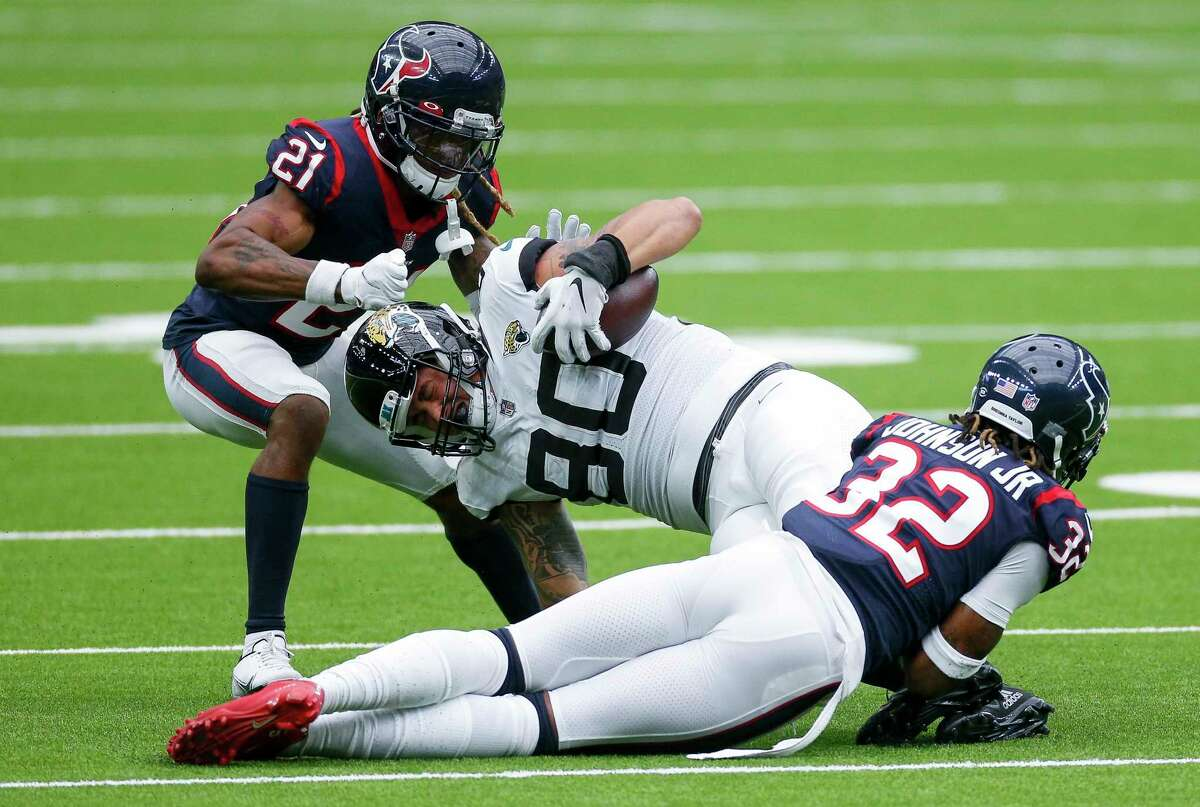 Houston Texans cornerbacks Lonnie Johnson (32) and Bradley Roby (21) tackle Jacksonville Jaguars tight end James O'Shaughnessy (80) during the fourth quarter of an NFL game at NRG Stadium on Sunday, Oct. 11, 2020, in Houston. The Texans won 30-14.