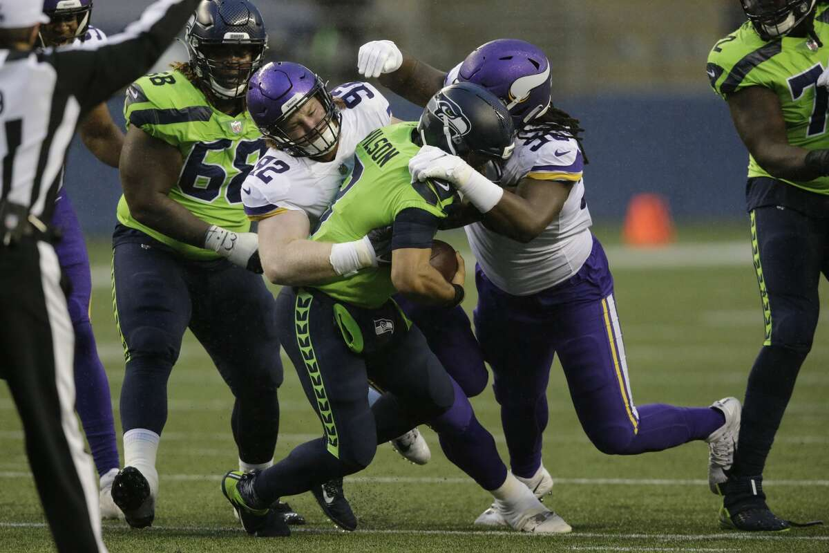 Minnesota Vikings James Lynch, left, and D.J. Wonnum, right, sack Seattle Seahawks quarterback Russell Wilson during the first half of an NFL football game, Sunday, Oct. 11, 2020, in Seattle. (AP Photo/John Froschauer)