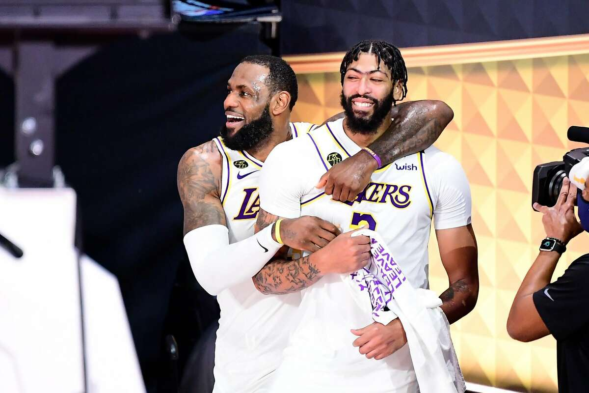 LAKE BUENA VISTA, FLORIDA - OCTOBER 11: LeBron James #23 of the Los Angeles Lakers and Anthony Davis #3 of the Los Angeles Lakers react after winning the 2020 NBA Championship in Game Six of the 2020 NBA Finals at AdventHealth Arena at the ESPN Wide World Of Sports Complex on October 11, 2020 in Lake Buena Vista, Florida. NOTE TO USER: User expressly acknowledges and agrees that, by downloading and or using this photograph, User is consenting to the terms and conditions of the Getty Images License Agreement. (Photo by Douglas P. DeFelice/Getty Images)