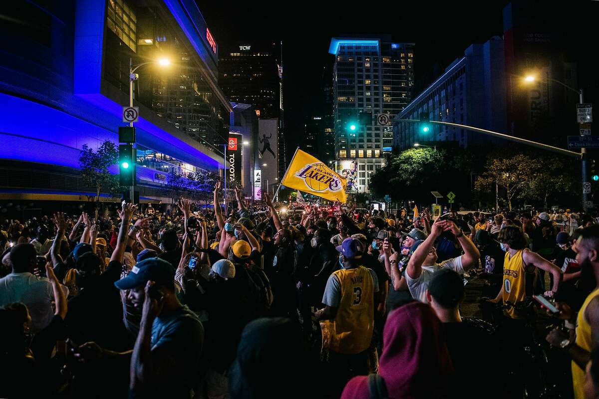 LOS ANGELES, CA - OCTOBER 11: Lakers fans celebrate in front of the Staples Center in on October 11, 2020 in Los Angeles, California. People gathered to celebrate after the Los Angeles Lakers defeated the Miami Heat in game 6 of the NBA finals. (Photo by Brandon Bell/Getty Images)