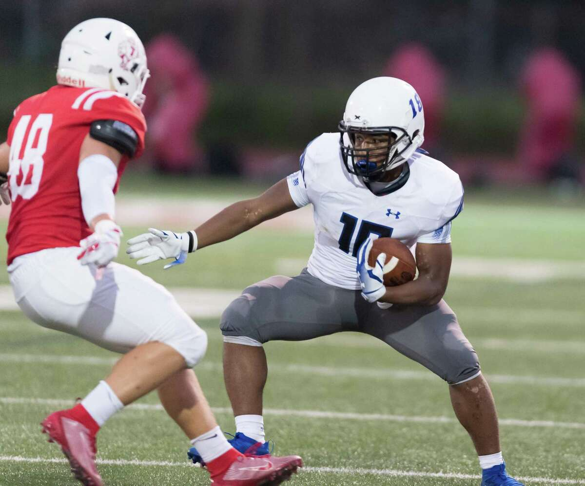 Trinity Christian Tigers Running Back, Emari Matthews (18) attempts get away from St. Thomas Eagles Linebacker, Vincent Ori (48) in the first half in a high school football game on Friday, September 27, 2019 at St. Thomas High School's Granger Stadium in Houston Texas.