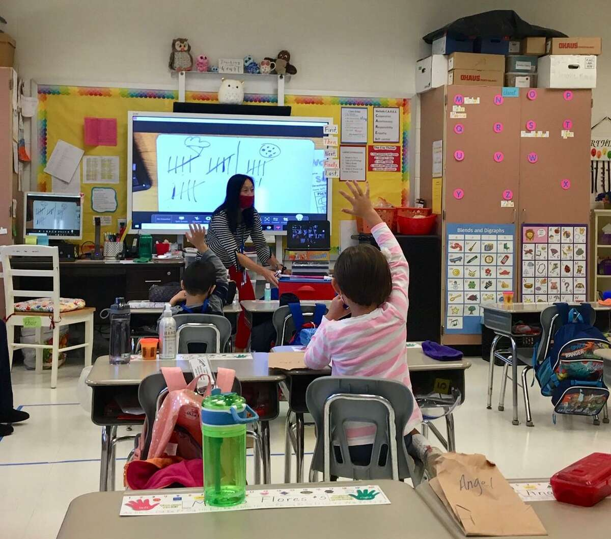 First-grade teacher Dung Stafford instructs both students in the classroom at Nichols Elementary School in Stratford and those at home on Thursday, Oct. 8, 2020.