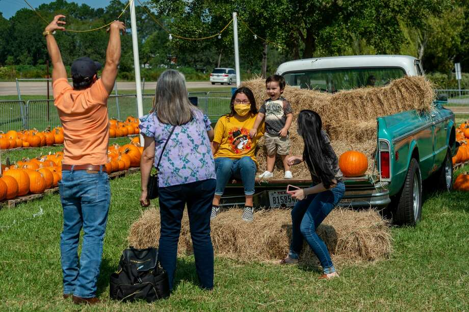 A family takes photos on the back of an antique pickup truck in the patch. The Pumpkin Patch at Wesley United Methodist Church opened for the season on Sunday at noon. They have a variety of pumpkins and various stations visitors can use for making fall-themed family photos while shopping. The pumpkin patch is open until October 31st, Mondays-Fridays 4pm-8pm, Saturdays 9am-8pm, and Sundays 12pm-8pm. The pumpkin patch is located at the intersection of Major and Folsom Drives in Beaumont. Photo made on October 11, 2020. Fran Ruchalski/The Enterprise Photo: Fran Ruchalski/The Enterprise / © 2020 The Beaumont Enterprise