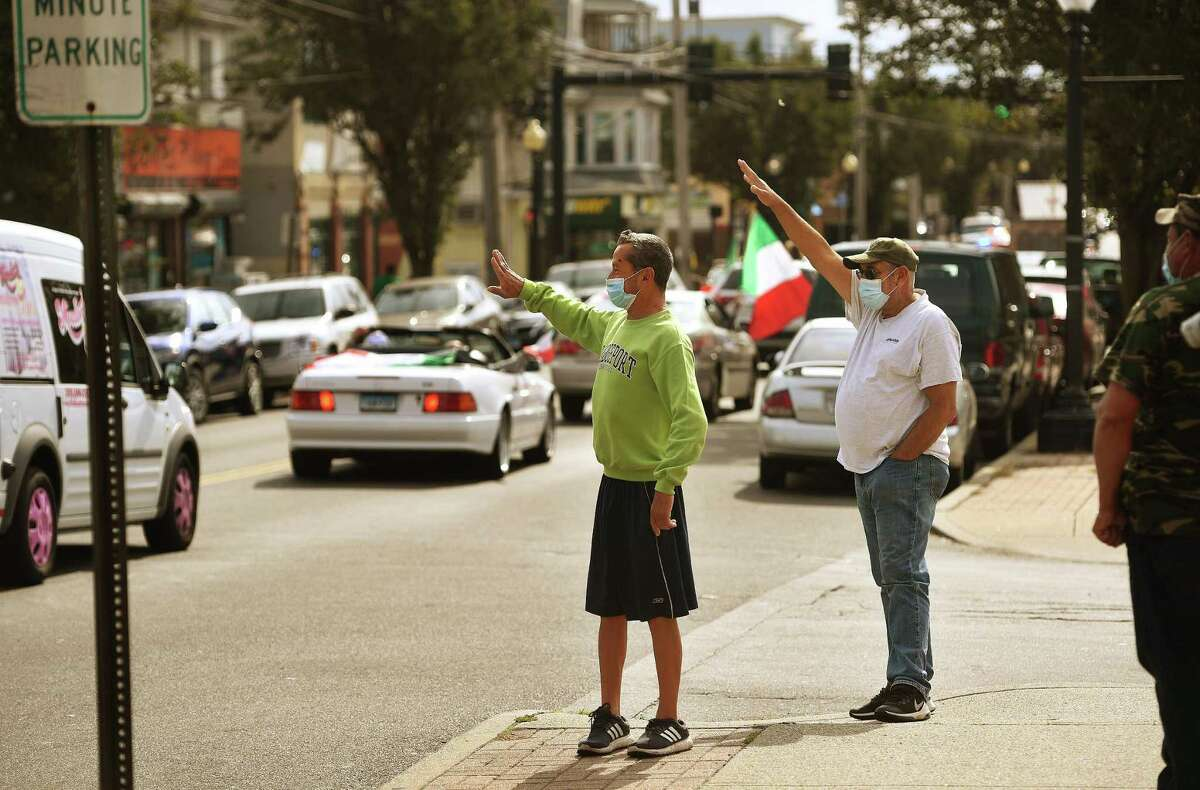 Carlos Granados, left, and Jose Santos, both of Bridgeport, attend the annual Columbus Day Parade on Madison Avenue in Bridgeport, Conn. on Sunday, October 11, 2020. This year's parade was scaled down dramatically due to the Covid-19 pandemic.