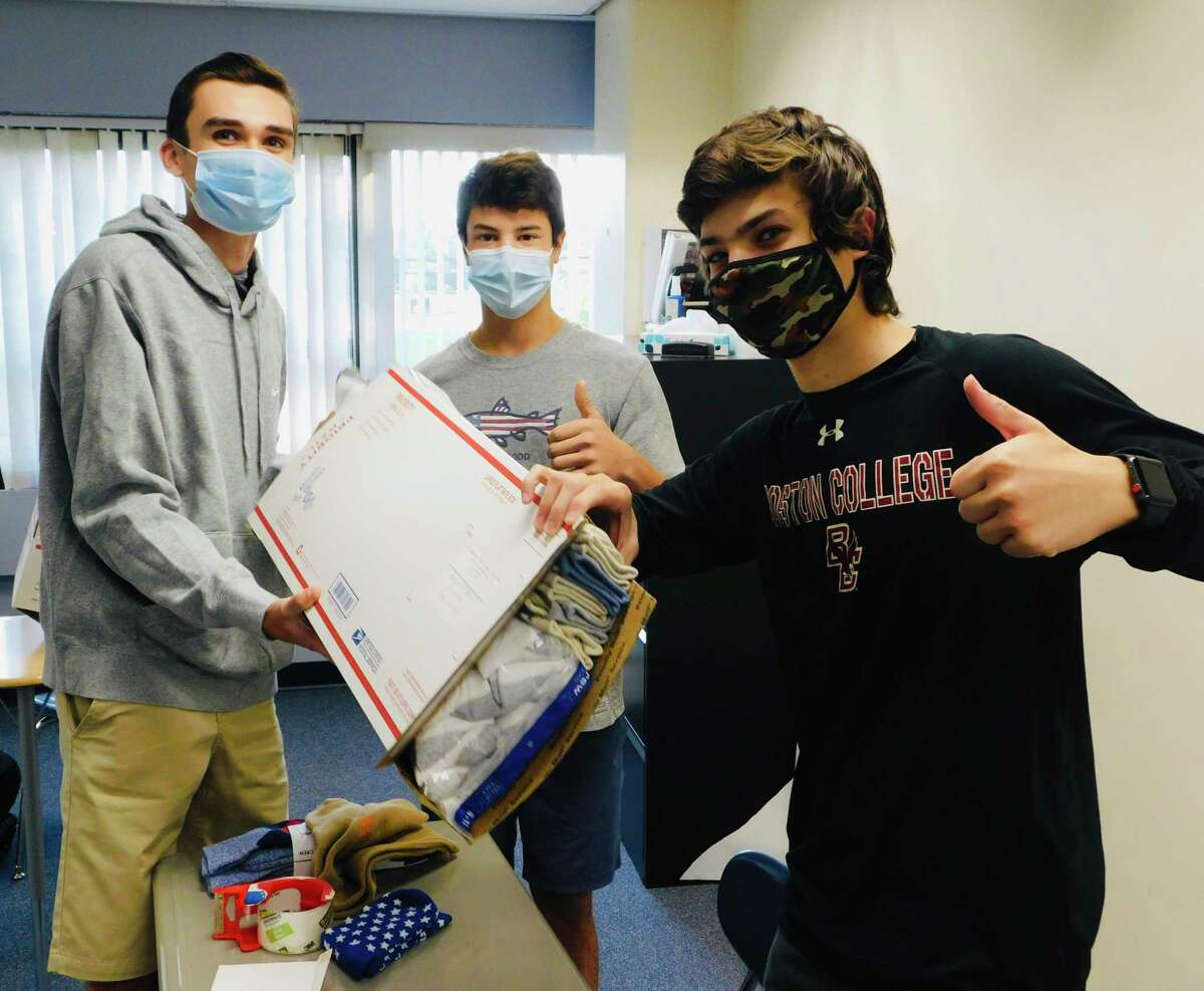 From left, Roen Crameri, Tyler Casey and Eli Ackerman, team leaders for Socks for Soldiers, stuff socks for mailing. The Wilton High School club sends socks for enlisted men and women and veterans to Homes for the Brave in Bridgeport, Kick for Nick in Wilton, and Provisions for Patriots Program in Georgia.
