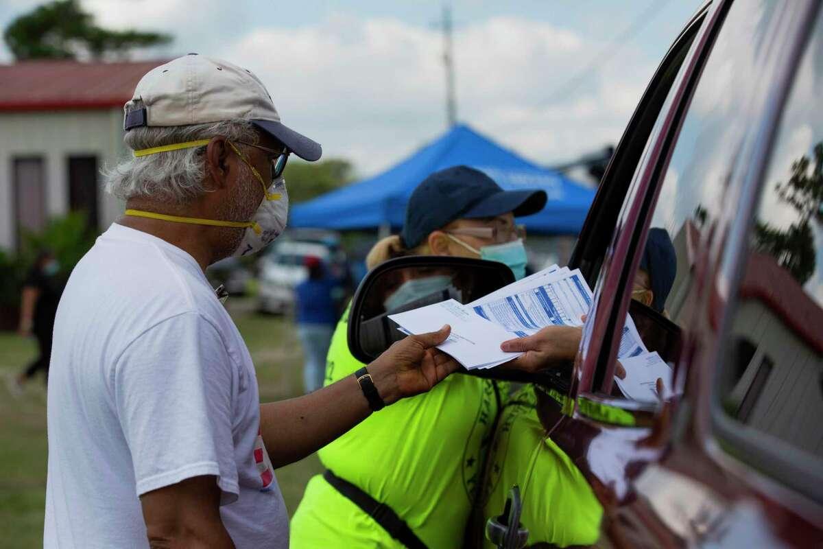 Muhammed Nasrullah, 68, hands a voter Texas voter registration applications at a food distribution event, Friday, Sept. 25, 2020, in Houston. Nasrullah has been a voter registrar since 2004.