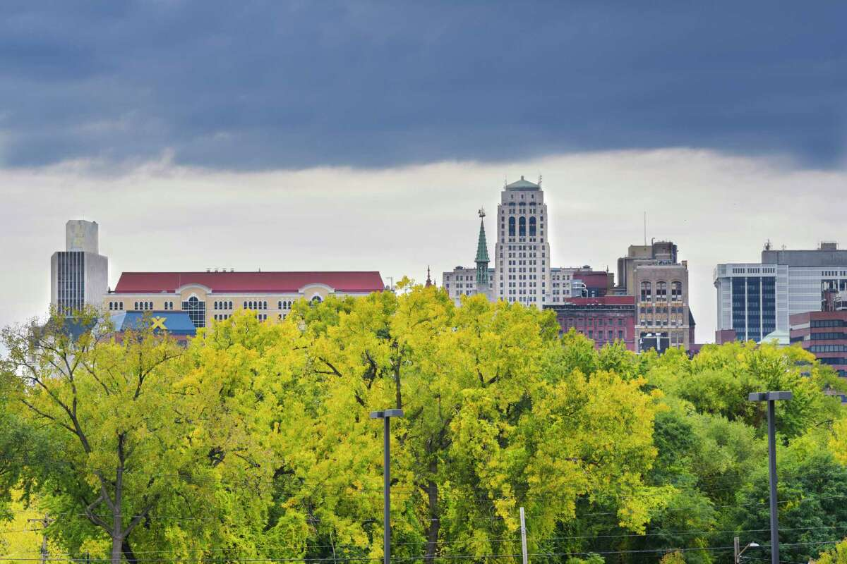 The leaves on trees near the Rensselaer Train Station are changing color as the Albany City skyline is seen in the background on Monday, Oct. 12, 2020, in Rensselaer, N.Y. (Paul Buckowski/Times Union)