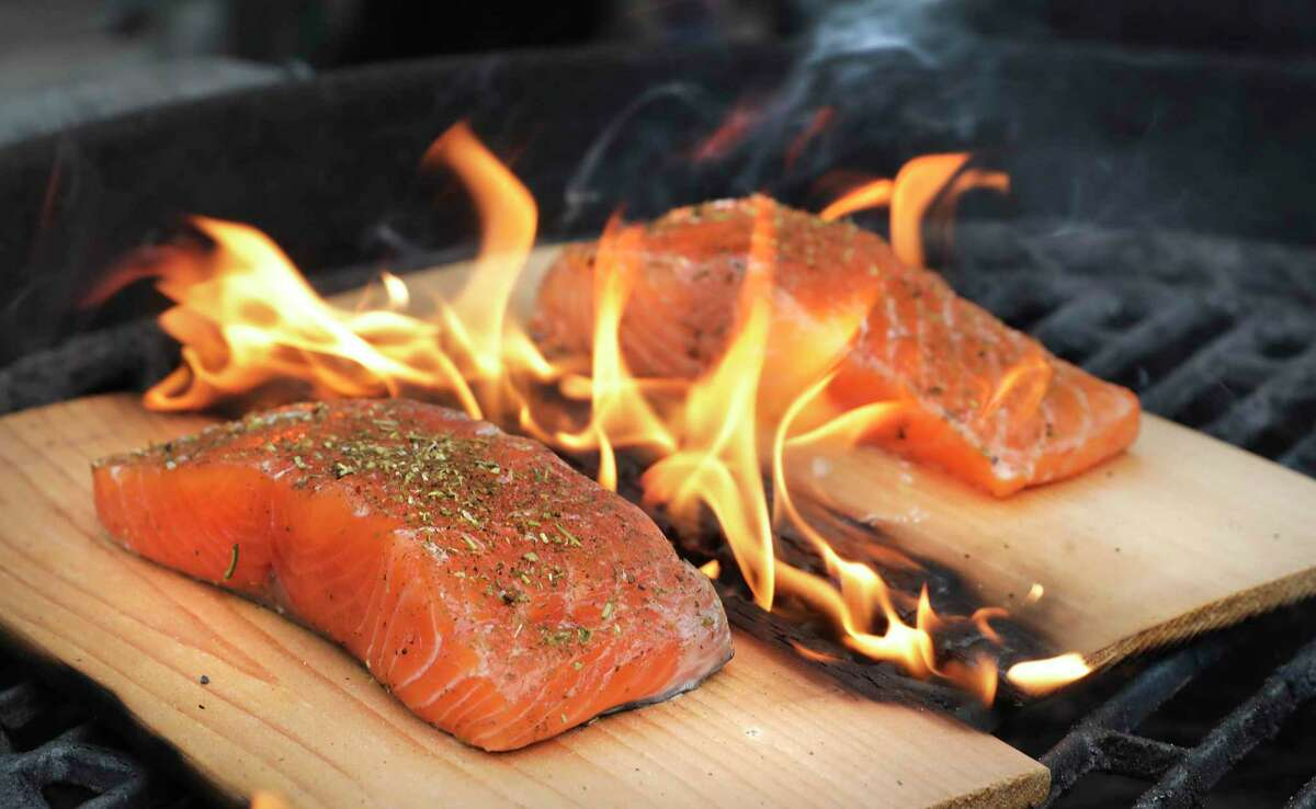 Salmon cooking on cedar planks over a hot grill fire.