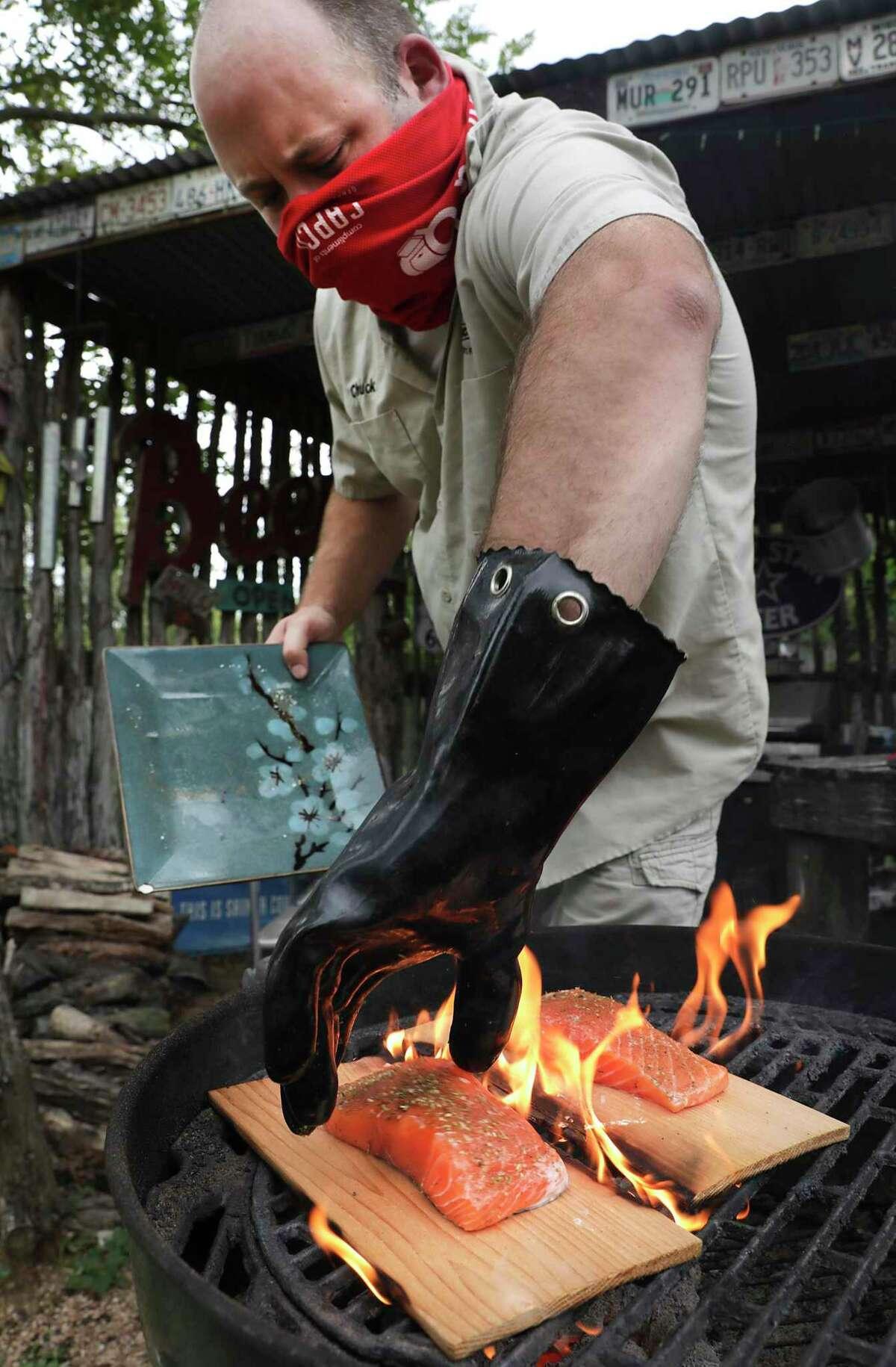 Chuck Blount cooks salmon on cedar planks over a hot grill fire.