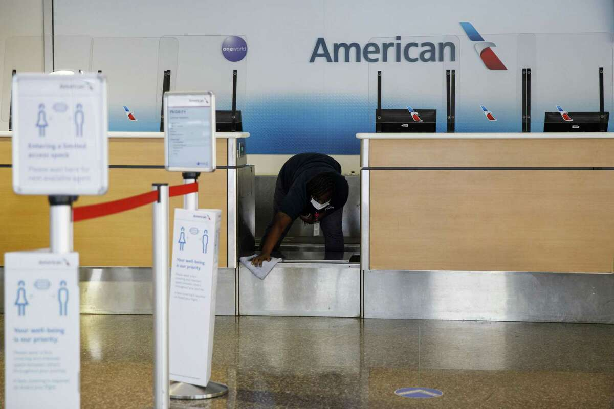 A worker cleans an American Airlines Group Inc. check-in counter at Tulsa International Airport (TUL) in Tulsa, Oklahoma, U.S., on Thursday, Oct. 1, 2020. American Airlines Group Inc.andUnited Airlines Holdings Inc.will start laying off thousands of employees as scheduled, spurning Treasury SecretarySteven Mnuchin's appeal for a delay as he negotiates with Congress over an economic relief plan that includes payroll support for U.S. carriers. Photographer: Patrick T. Fallon/Bloomberg