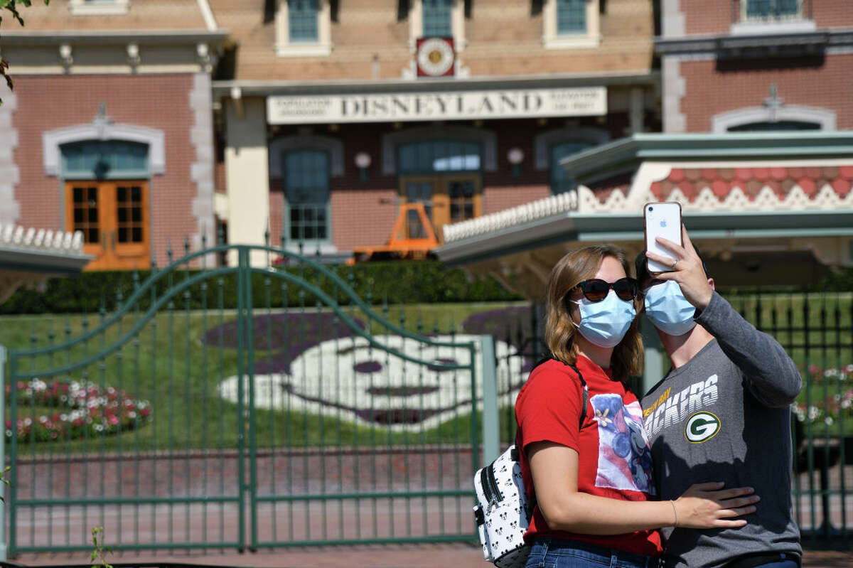 Alex Riedel takes a selfie with his wife Jaime Riedel in front of the closed Disneyland Main Gate in Anaheim, Calif., on Friday, October 2, 2020.