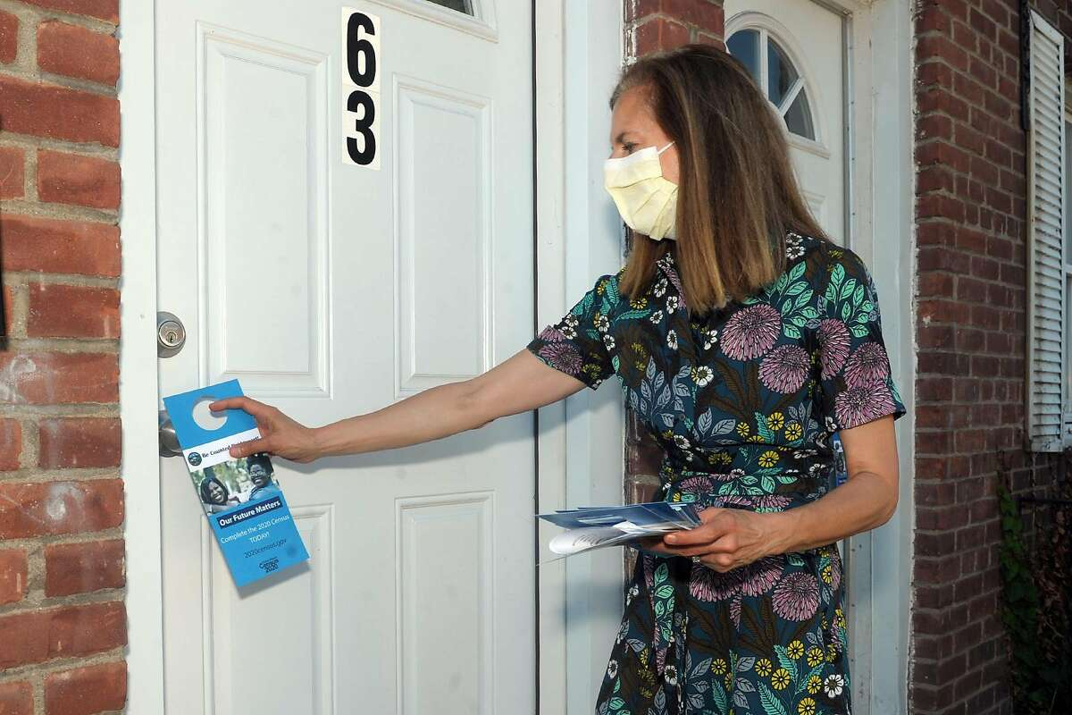 Lt. Gov. Susan Bysiewicz places informational material promoting the 2020 United States Census on doors in the Hollow neighborhood of Bridgeport, Conn., in June.