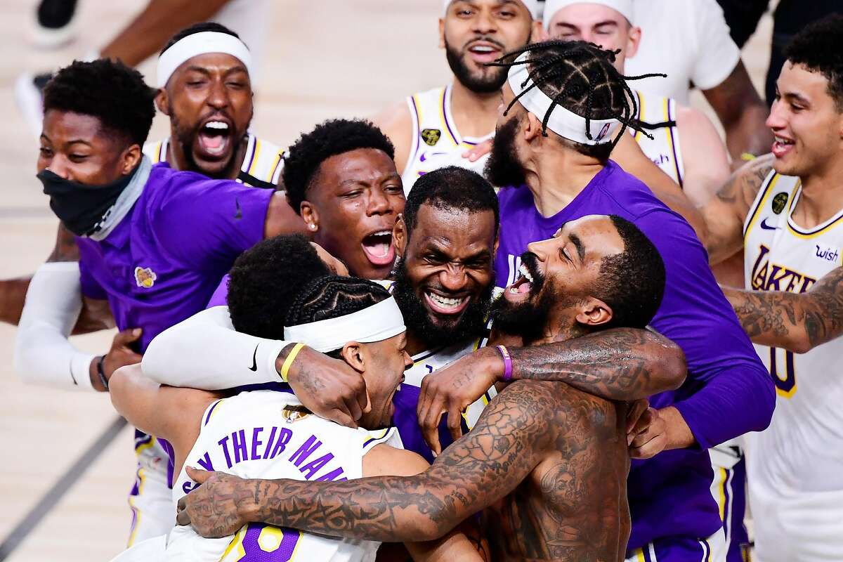 LAKE BUENA VISTA, FLORIDA - OCTOBER 11: LeBron James #23 of the Los Angeles Lakers celebrates with Quinn Cook #28 of the Los Angeles Lakers and teammates after winning the 2020 NBA Championship in Game Six of the 2020 NBA Finals at AdventHealth Arena at the ESPN Wide World Of Sports Complex on October 11, 2020 in Lake Buena Vista, Florida. NOTE TO USER: User expressly acknowledges and agrees that, by downloading and or using this photograph, User is consenting to the terms and conditions of the Getty Images License Agreement. (Photo by Douglas P. DeFelice/Getty Images) *** BESTPIX ***
