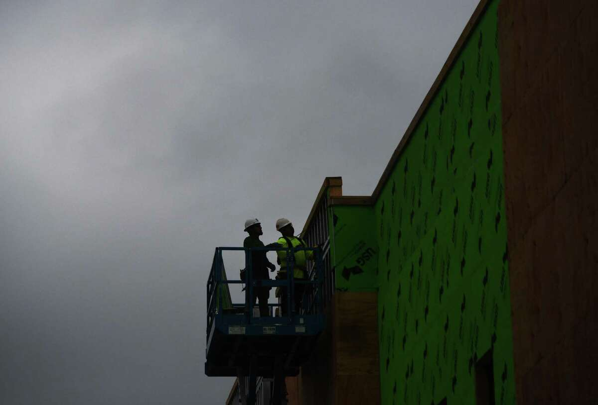 Rain clouds roll in as a construction crew works on a self storage unit at the intersection of West Avenue and Piave Street in Stamford, Conn. Thursday, June 11, 2020.