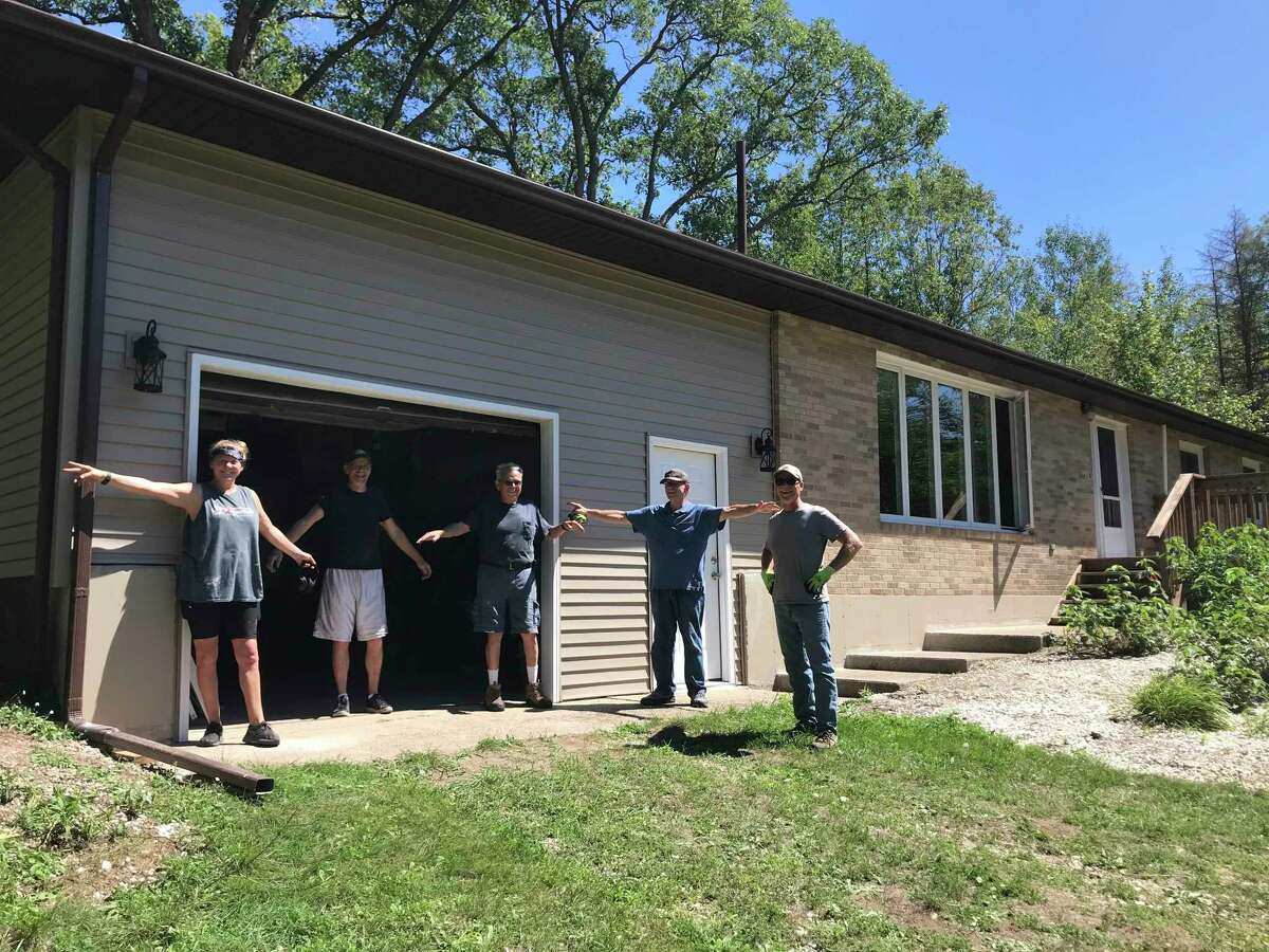 Ken Smith, along with his co-volunteers, celebrate the completion of a build project with Habitat for Humanity. Smith volunteers on builds and at the Restore in Big Rapids, and is on the American Red Cross disaster aid team helping victims of fires and other disasters. (Submitted photo)