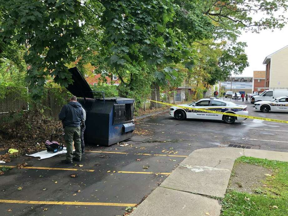 Officers are examining a car seat next to a dumpster blocked off by police tape. A baby girl was found inside the dumpster. Photo: William Lambert /