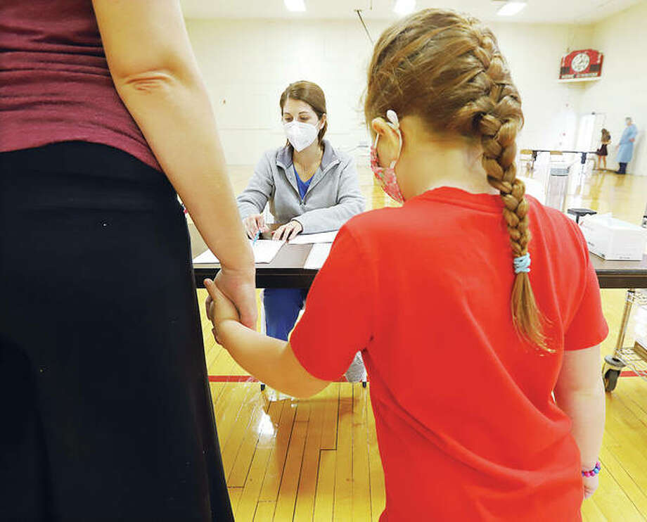 Five-year-old Lucy Colby of Granite City holds the hand of her mother, Danielle, on Monday in Alton as they are checked in by Southern Illinois University School of Dental Medicine records employee Christen Holman to get a free dental check-up at the school's annual Give Kids a Smile Day.