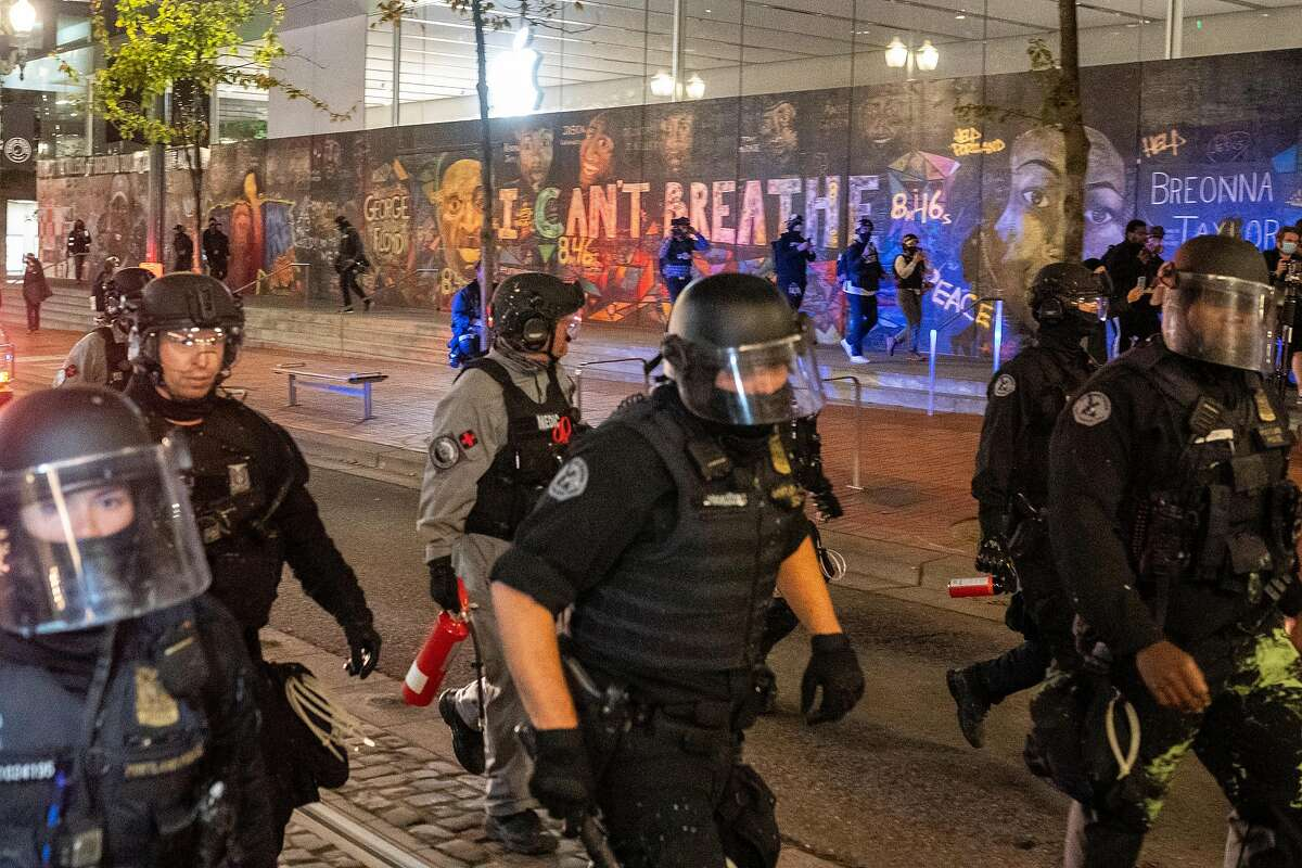 Portland, Ore., police disperse a crowd of protesters past a mural of George Floyd and Breonna Taylor in September.