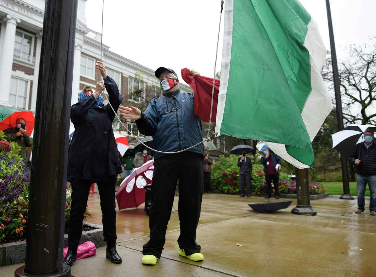 Town Ambassador at Large Bea Crumbine and St. Lawrence Society President Tod Laudonia hoist the Italian flag during the Columbus Day flag Italian raising outside Town Hall in Greenwich, Conn. Monday, Oct. 12, 2020. Former Selectman Peter Crumbine and Town Ambassador at Large Bea Crumbine were honored for their contributions to the community at the ceremony.