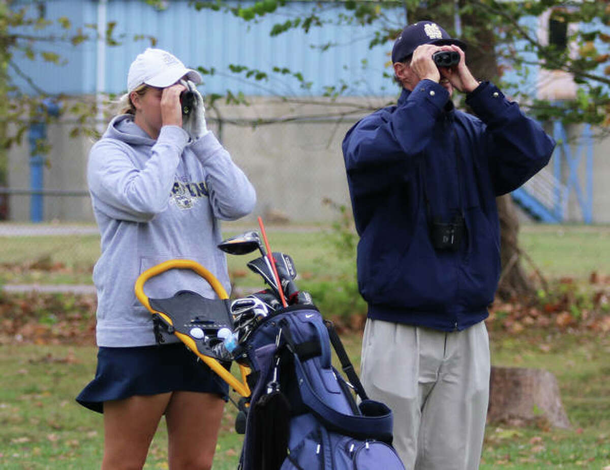 Father McGivne's Julia Stobie, left, and coach Ken Hyten scope out the hole during the Class 1A Salem Sectional.