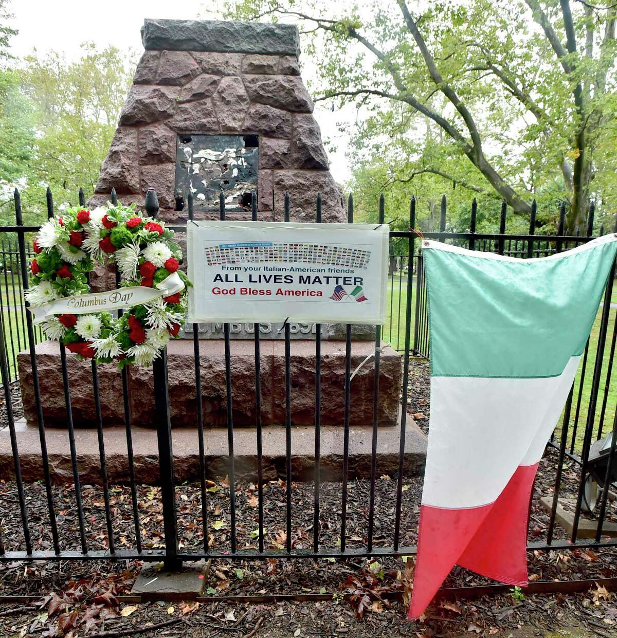 Members of various Italian-American heritage clubs and societies in the New Haven area and supporters from Bridgeport put up a wreath, a sign and an Italian flag this year at the pedestal of the removed statue of Christopher Columbus on Wooster Square Park in New Haven to commemorate Columbus Day.