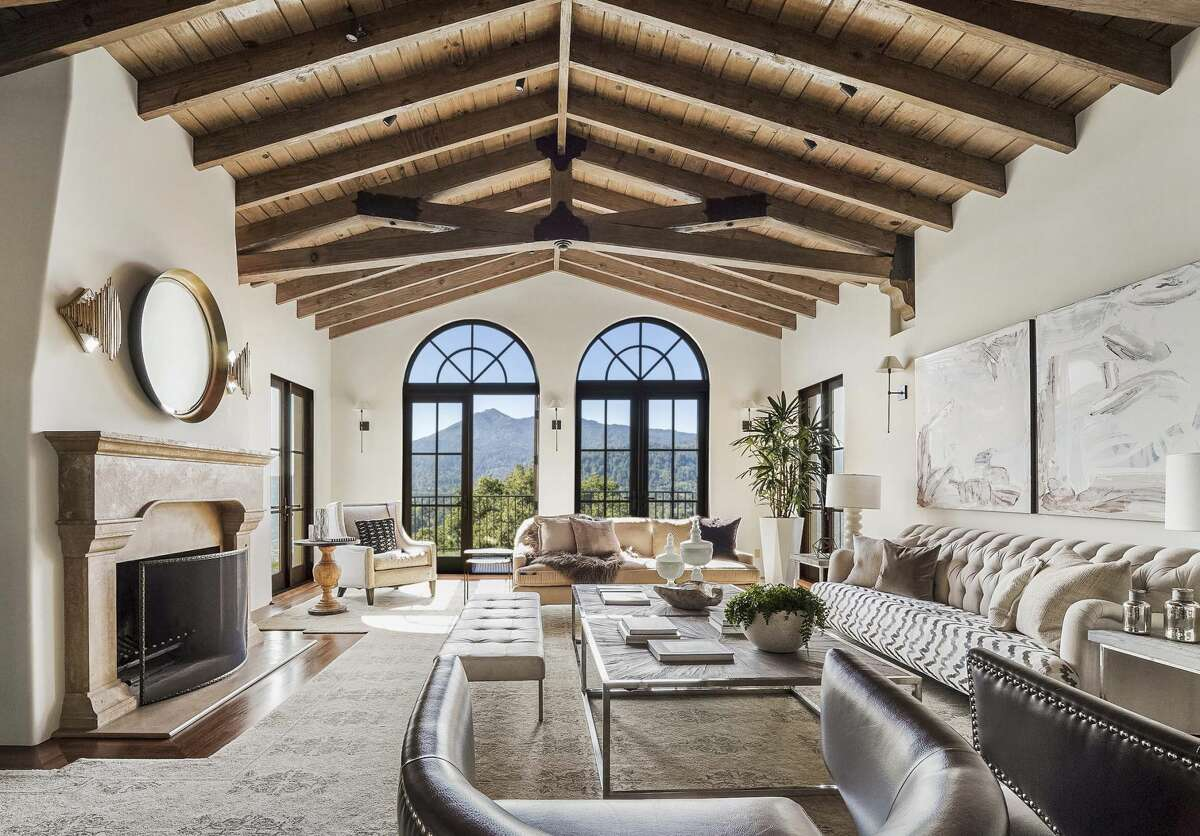 The living room has 14-foot beamed ceilings and a stone fireplace, as well as views of Mount Tamalpais from the windows and balcony.