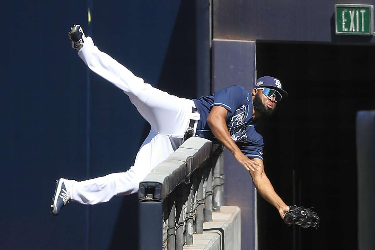 Tampa Bay's Manuel Margot, a former Padre, catches a foul ball as he crashes over the wall in San Diego.