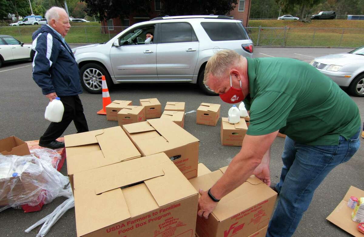 Derby Mayor Richard Dziekan and Oxford First Selectman George Temple, left, join in with members of TEAM Inc., and volunteers from the YMCA to load up food into awaiting vehicles at Nolan Field's parking lot in Ansonia, Conn., on Tuesday Oct. 6, 2020. Farmers to Family arranged the free food distribution for valley families. Each family will receive 12 pounds of produce, 5 pounds of meat, 5 pounds of dairy and a gallon of milk. About 1,200 boxes were given out.