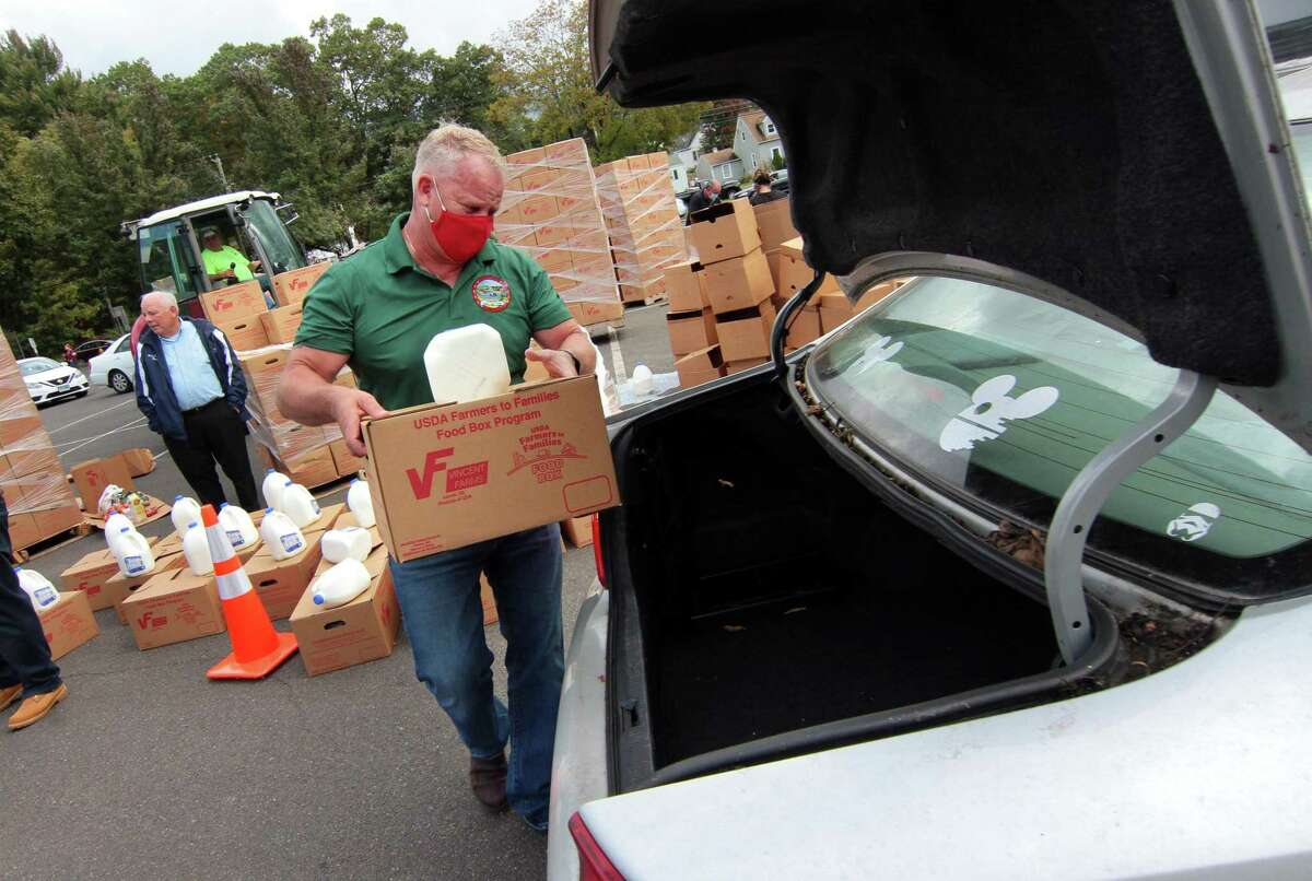 Members of TEAM Inc., volunteers from the YMCA, and local politicians load up food into awaiting vehicles at Nolan Field's parking lot in Ansonia, Conn., on Tuesday Oct. 6, 2020. Farmers to Family arranged the free food distribution for valley families. Each family will receive 12 pounds of produce, 5 pounds of meat, 5 pounds of dairy and a gallon of milk. About 1,200 boxes were given out.