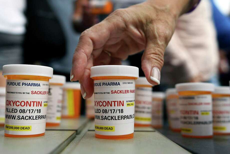 FILE - In this Aug. 17, 2018, file photo, family and friends who have lost loved ones to OxyContin and opioid overdoses leave pill bottles in protest outside the headquarters of Purdue Pharma, which is owned by the Sackler family, in Stamford, Conn. OxyContin maker Purdue Pharma should not be able to make any more political contributions without a judge's permission, lawyers for its creditors said in a Friday, July 10, 2020 court filing. (AP Photo/Jessica Hill, File) Photo: Jessica Hill / Associated Press / Copyright 2018 The Associated Press. All rights reserved
