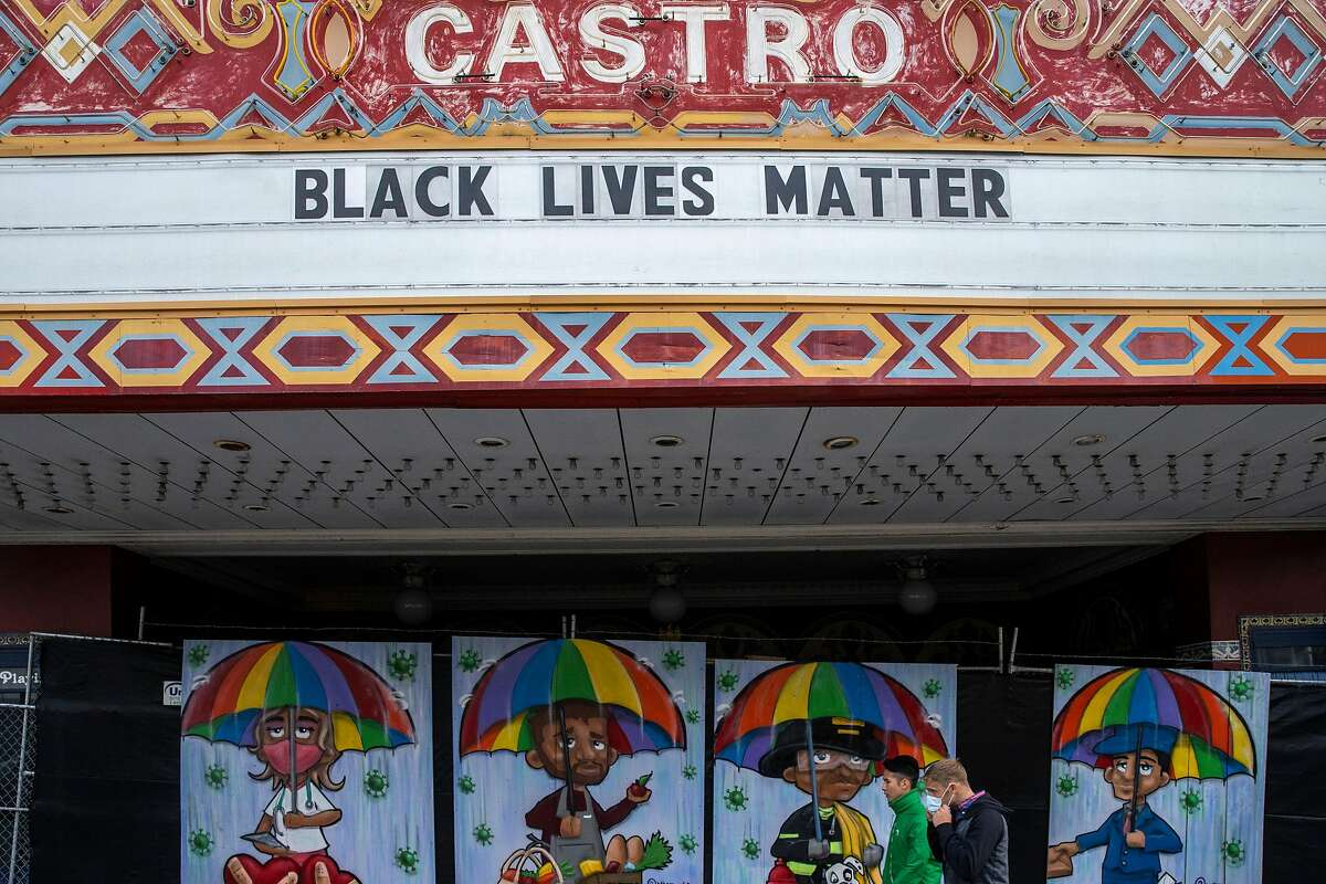 People walk past the boarded up Castro Theatre on Saturday, June 20, 2020, in San Francisco, Calif. After being closed due to the coronavirus pandemic, movie theaters in several Bay Area counties are reopening this week.