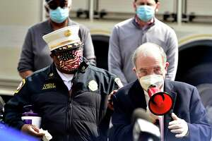 New Haven, Connecticut - Monday, May 18, 2020: State Senator Martin Looney, with megaphone, New Haven Mayor Justin Elicker, Lieutenant Governor Susan Bysiewicz, some members of the Board of Alders, state senator Martin Looney, speaking on megaphone, the New Haven Fire and Police departments honor and salute EMS workers at American Medical Response on Middletown Ave. with a drive-by parade Monday morning in New Haven during annual National EMS Week. EMS Week Salute with Mayor Elicker and Lieutenant Governor Bysiewicz Joined with Members of the Board of Alders, State Delegation and the New Haven Fire and Police DepartmentsCoronavirus / Covid-19 pandemic.