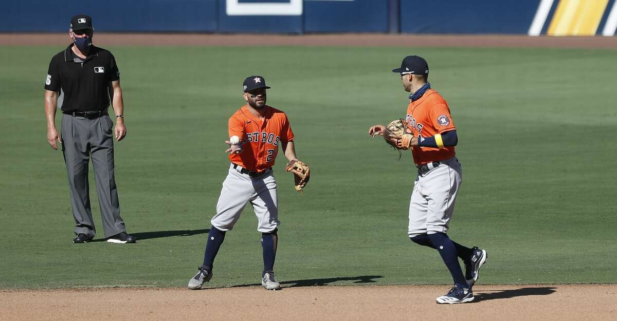 Houston Astros shortstop Carlos Correa (1) and second baseman Jose Altuve (27) swapped positions while Tampa Bay Rays Brandon Lowe (8) batted during the fifth inning of Game 2 of the American League Championship Series at Petco Park, Monday, October 12, 2020, in San Diego.