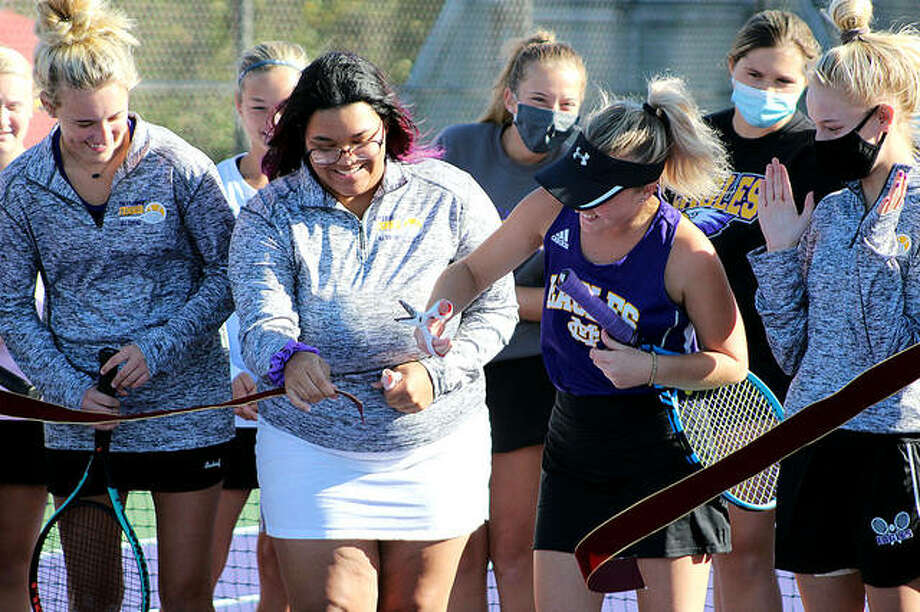 CM tennis players, from left, Addie Callies, Maya Wimberly and Kennedy Loewen celebrate as Loewen cuts the ribbon opening the school's refurbished courts Monday in Bethalto. The ceremony took place prior to CM's regular-season finale against Greenville. The match was the first at CM in three years because of deterioration on the on-campus courts. For the Eagles seniors, it was their first, and last, match at home. The Eagles played their home matches at Gordon Moore Park the last three seasons.