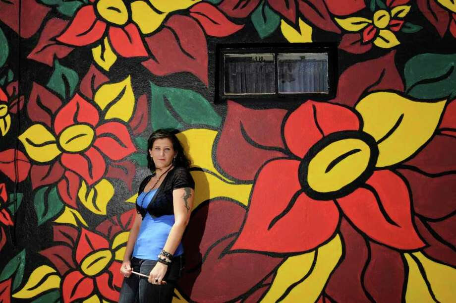 Artist Stephanie Levay stands with a mural she painted on a blank wall of The Closet Shop, a designer consignment on Delaware Avenue in Delmar. The mural took Levay nine days to complete. ( Michael P. Farrell / Times Union ) Photo: Michael P. Farrell