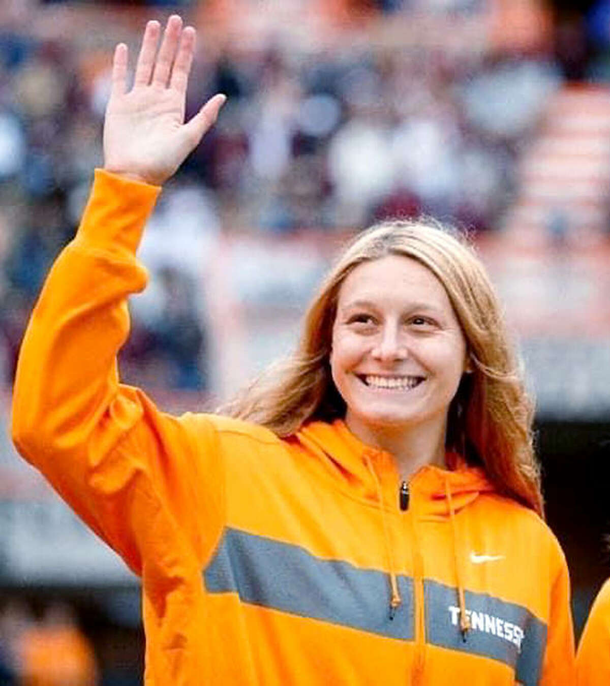 University of Tennessee swimmer Bailey Grinter waves to a packed Neyland Stadium in Knoxville after she and her teammates were introduced to the crowd.