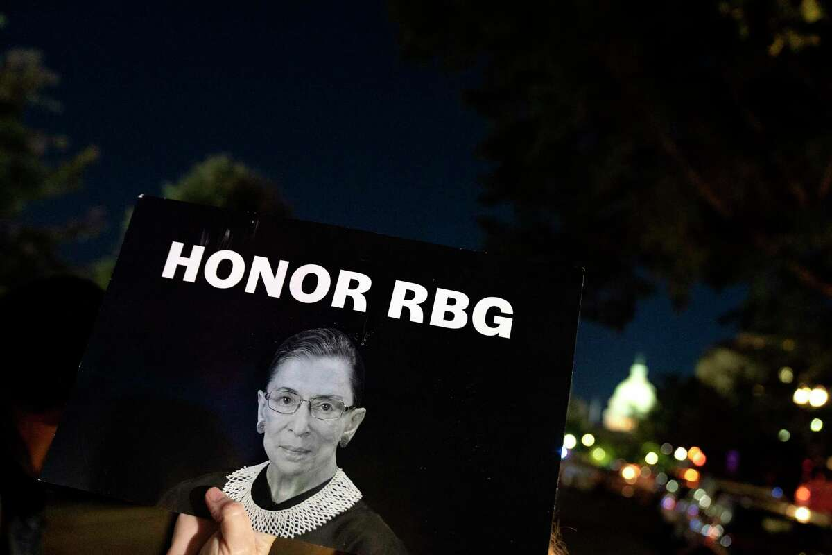 A protester holds a sign with a picture of Ruth Bader Ginsburg.