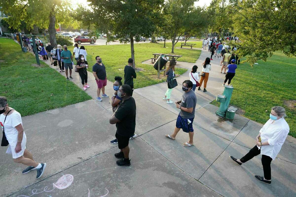 People wait in a long line that wraps around the baseball field outside at the Metropolitan Multi-Services Center, 1475 W. Gray St., on the first day of early voting Tuesday,October13, 2020. In Houston.