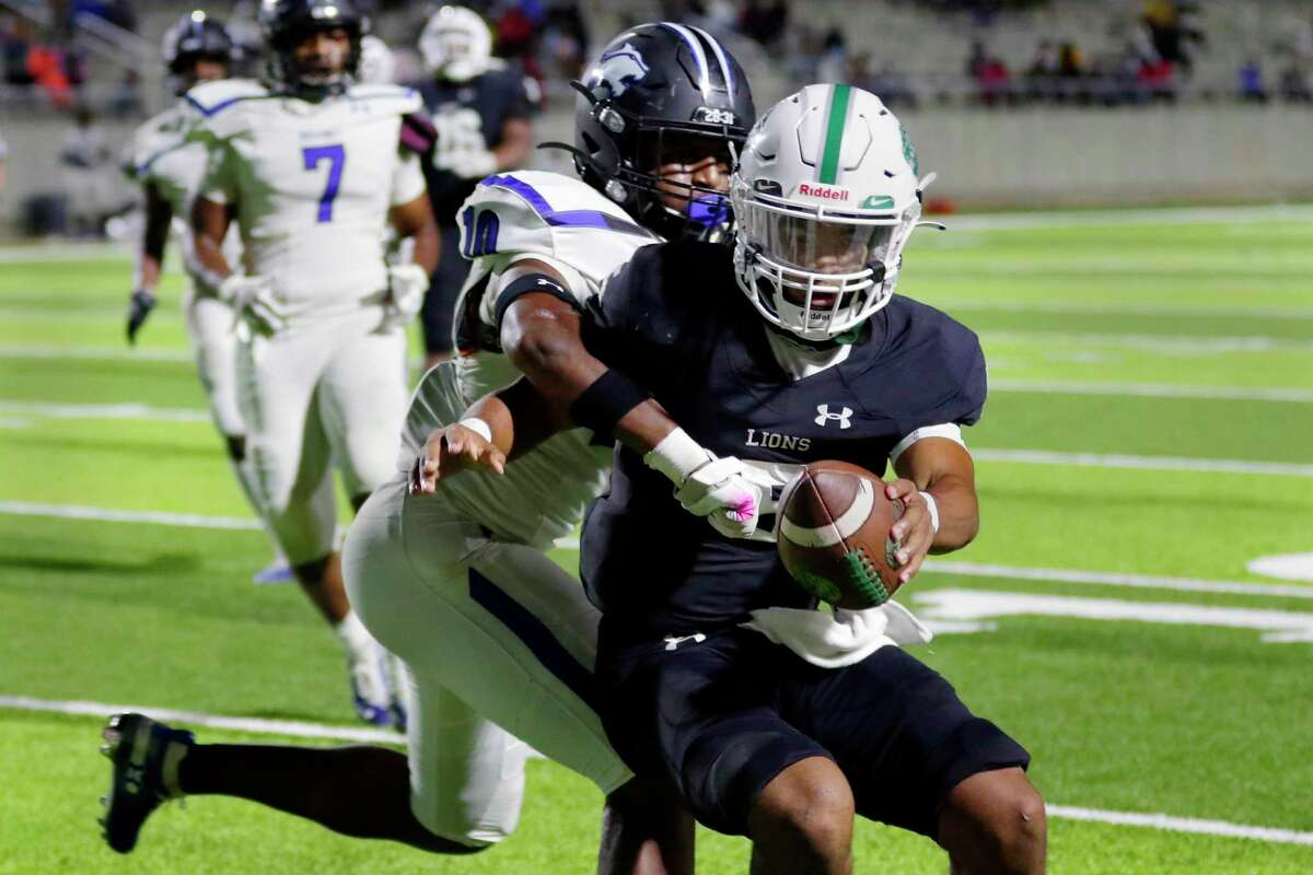 Spring quarterback Bishop Davenport, right, breaks the tackle attempt by Dekaney receiver Ronnie McNeal (10) to score during the second half of the District 14-6A opener Friday, Oct. 9, at Planet Ford Stadium.