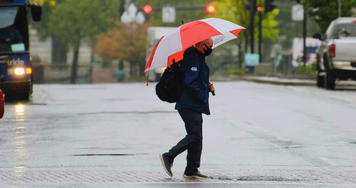 A man uses and umbrella to cover himself from the rain as he walks across State Street on Tuesday, Oct. 13, 2020, in Albany, N.Y. (Paul Buckowski/Times Union)