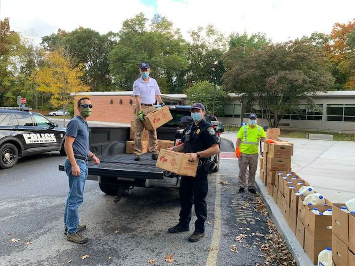 Police officers and Parks and Recreation workers unload food boxes for distribution to Wilton residents in need on Oct. 13, 2020.