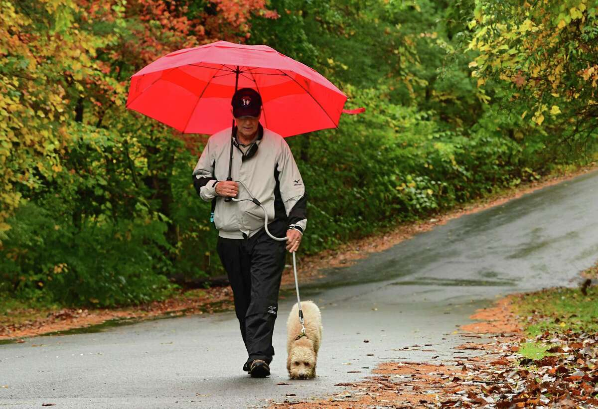 Doug Hasbrouck of Glenmont walks his granddaughter's dog Oliver who enjoys the petrichor of the freshly fallen rain on Tuesday, Oct. 13, 2020 in Albany, N.Y. (Lori Van Buren/Times Union)