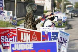 People walk by signs outside the Metropolitan Multi-Services Center, 1475 W. Gray St., during the first day of early voting Tuesday, Oct. 13, 2020 in Houston.