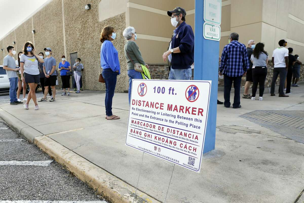 Voters wait in a line that snakes around the corner of the building outside of the Trini Mendenhall Community Center as early voting begins Tuesday, Oct. 13, 2020 in Houston, TX.