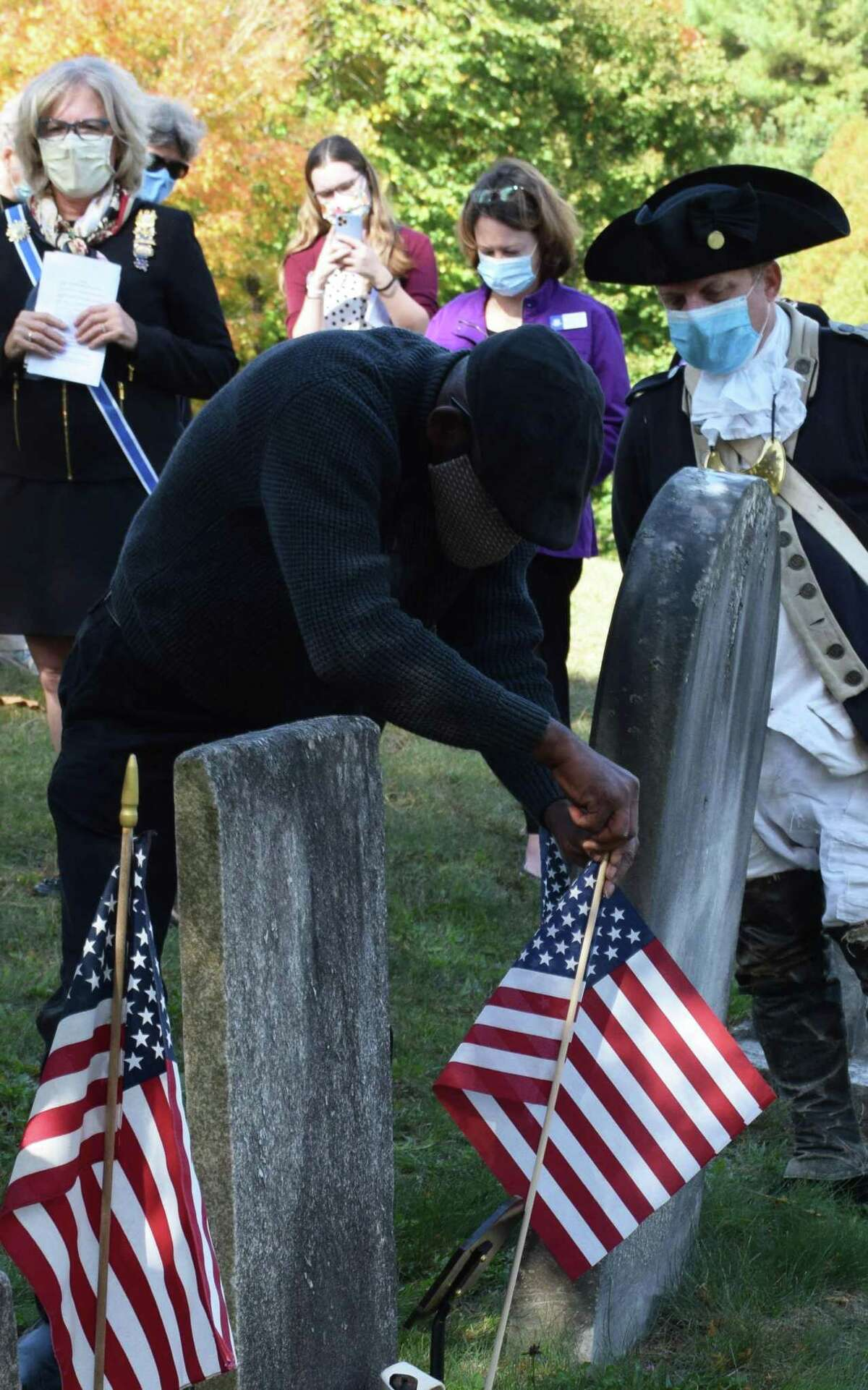 William Fothergill of Hartford, a descendant of Samuel and Jeruel Phillips, places an American flag at the grave sites.