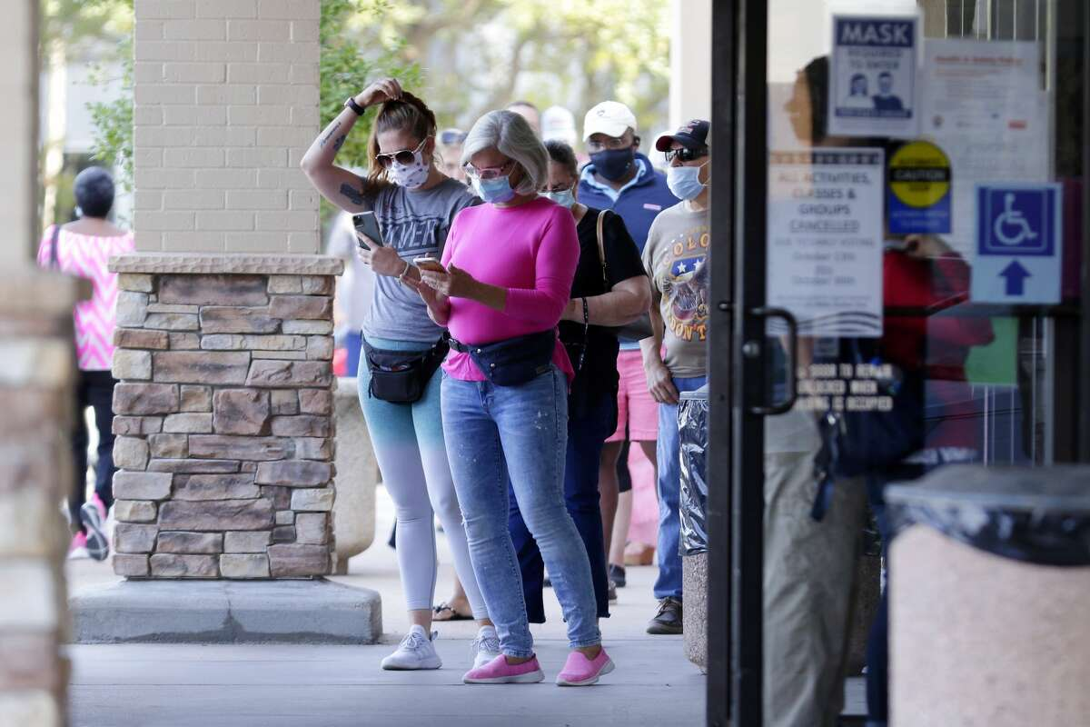 Voters wait near the entrance in a line that snakes around the corner of the building outside of the Trini Mendenhall Community Center as early voting begins Tuesday, Oct. 13, 2020 in Houston, TX.