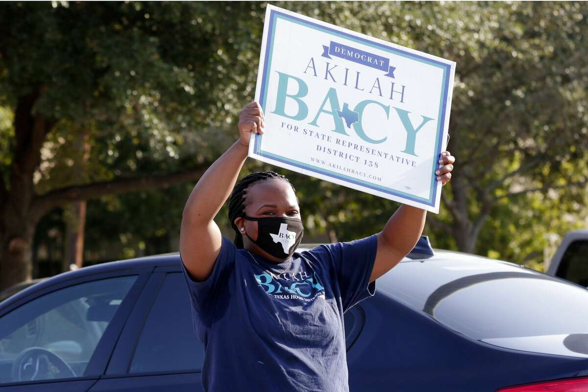 Candidate Akilah Bacy waves her campaign sign to voters outside of the Trini Mendenhall Community Center as early voting begins Tuesday, Oct. 13, 2020 in Houston, TX.