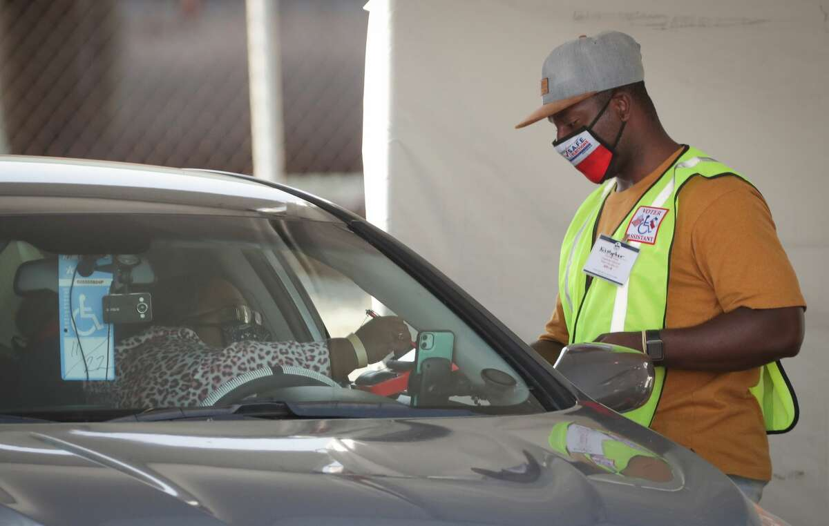 A Voter Assistant aids a drive-thru voter a the Houston Food Bank, which is operating an early voting site for the first time Tuesday, Oct. 13, 2020, in Houston.